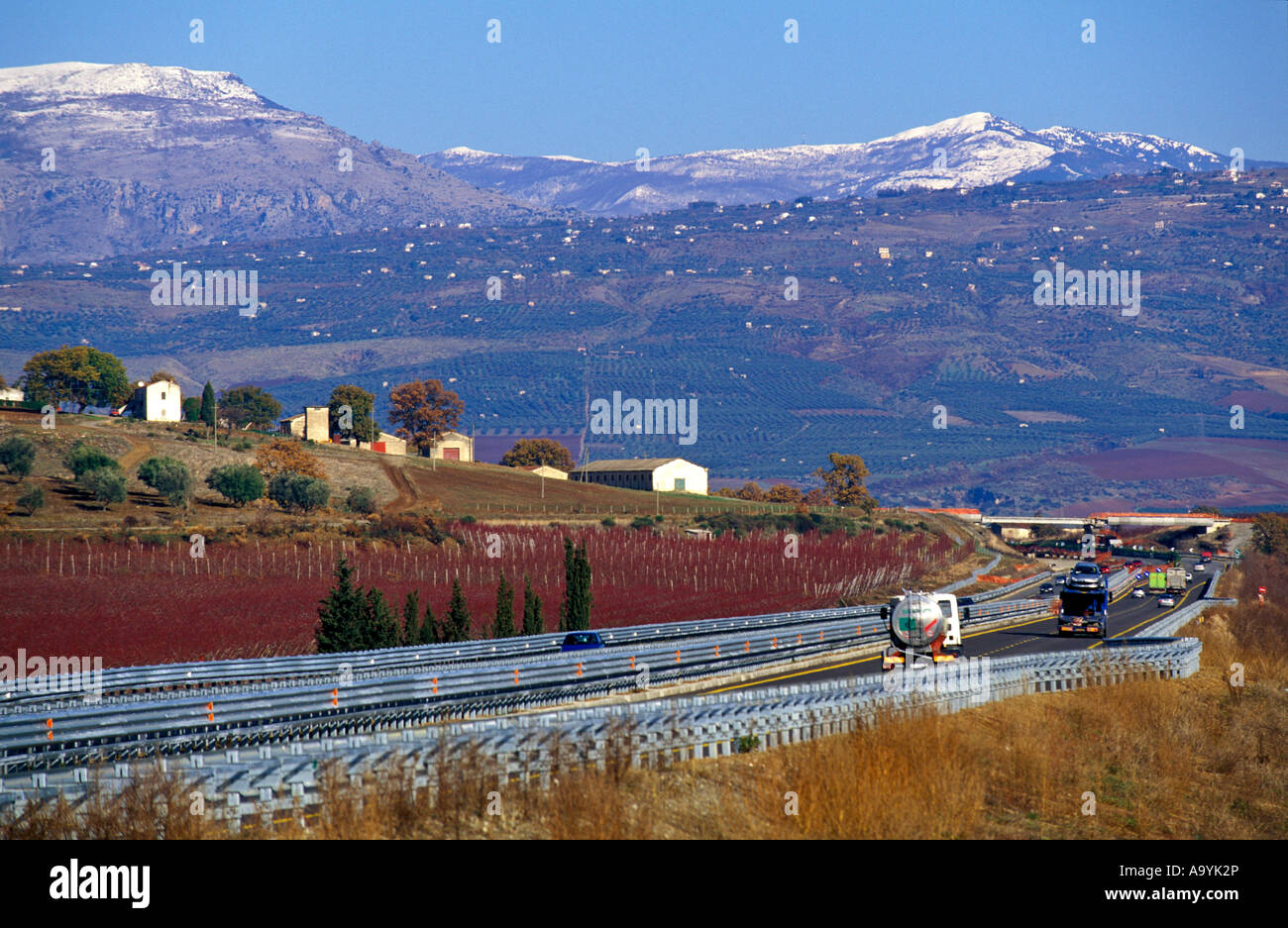 Freeway Strada del Sole and village with snow capped Pollino mountains, Calabria, Italy - Stock Image