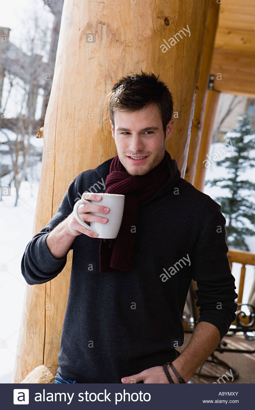 Young man with a warm drink - Stock Image