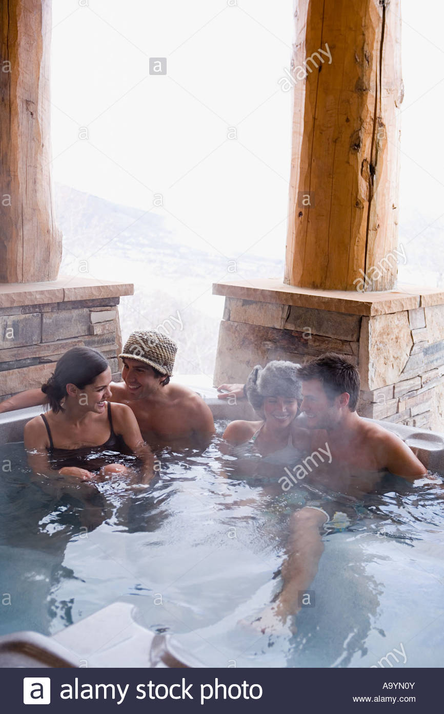 Friends in a hot tub - Stock Image
