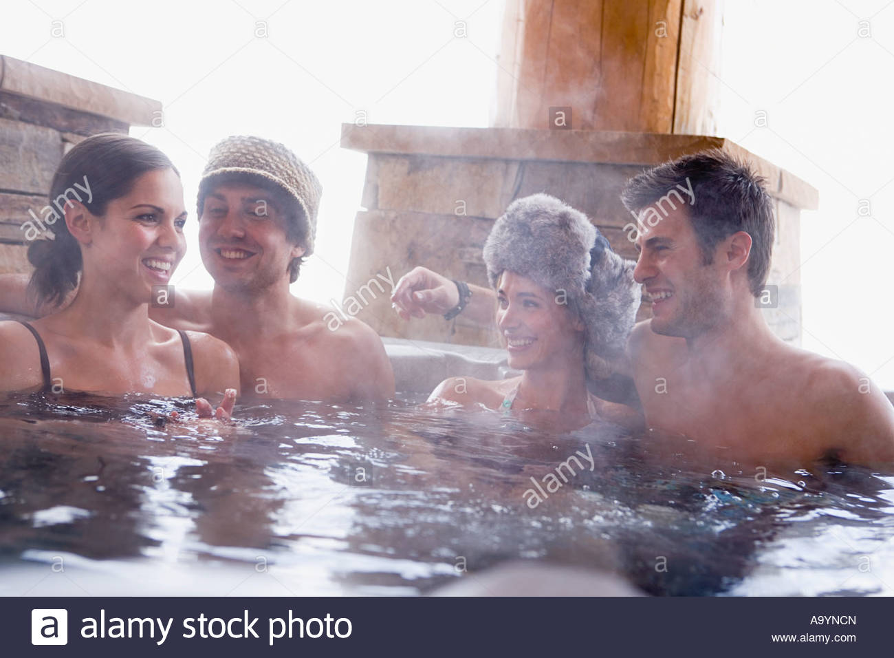 Young couples in a hot tub - Stock Image