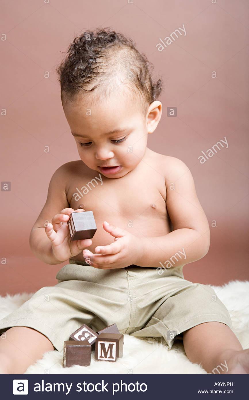 Baby boy looking at building block - Stock Image