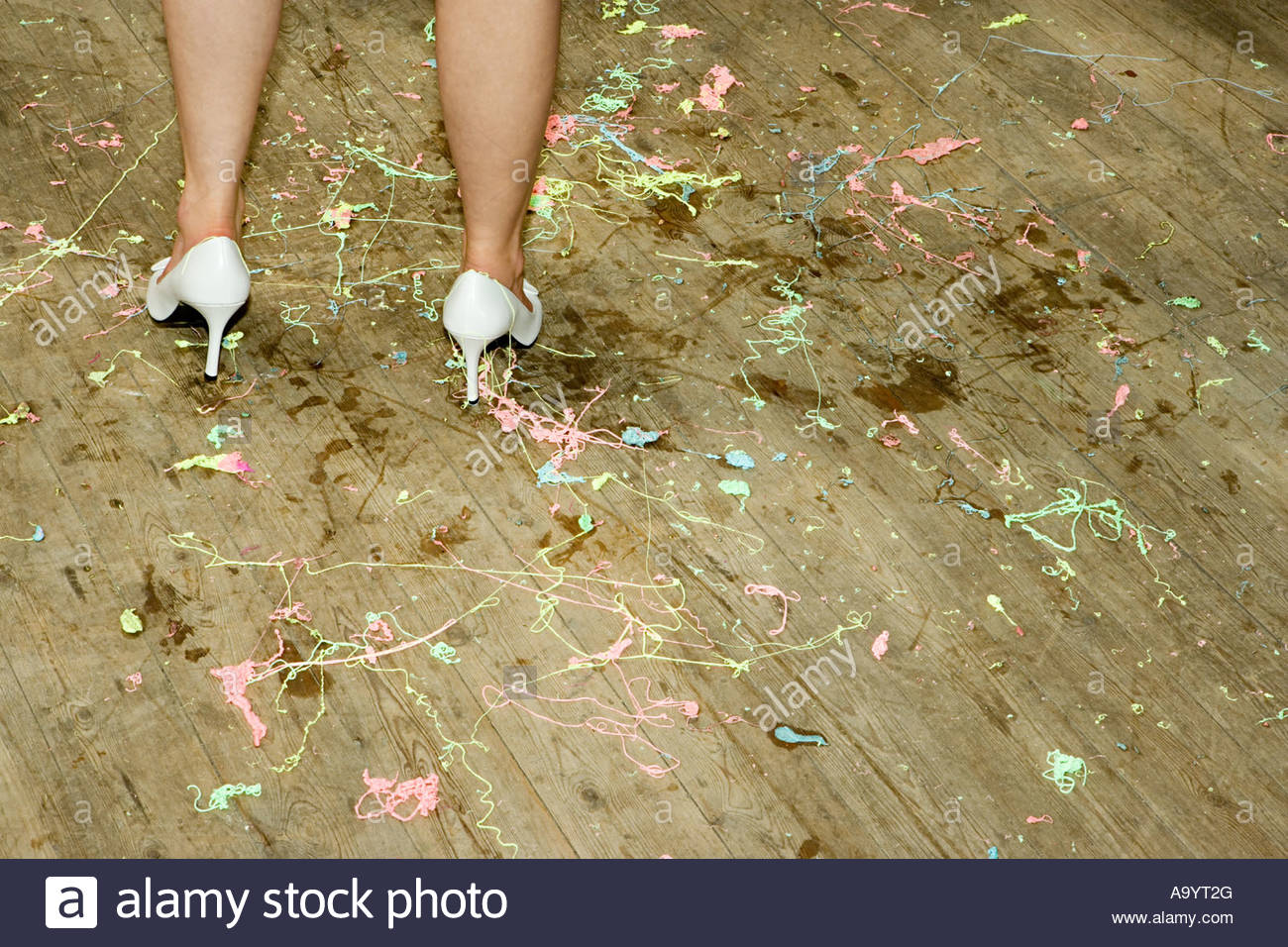 Woman standing on a messy floor - Stock Image