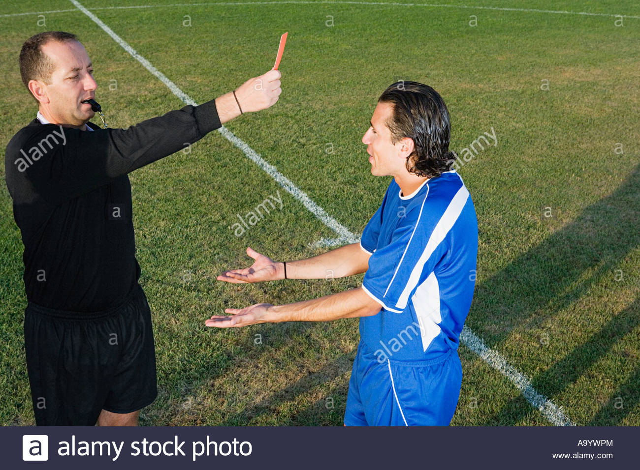 Referee showing footballer red card - Stock Image