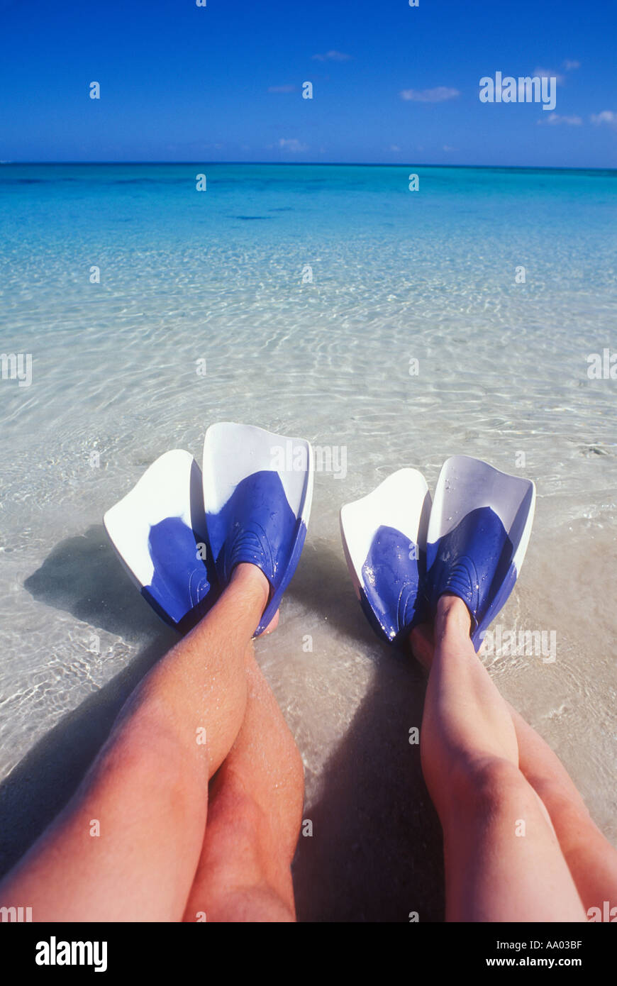 Couples legs sitting in shallow water wearing swim fins Fiji South Pacific Ocean Model released image - Stock Image