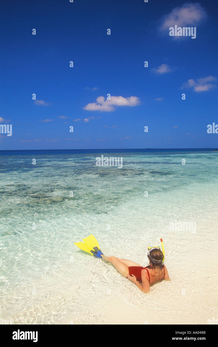 Woman in swimsuit resting in shallow water Maldives Indian Ocean model released image - Stock Image