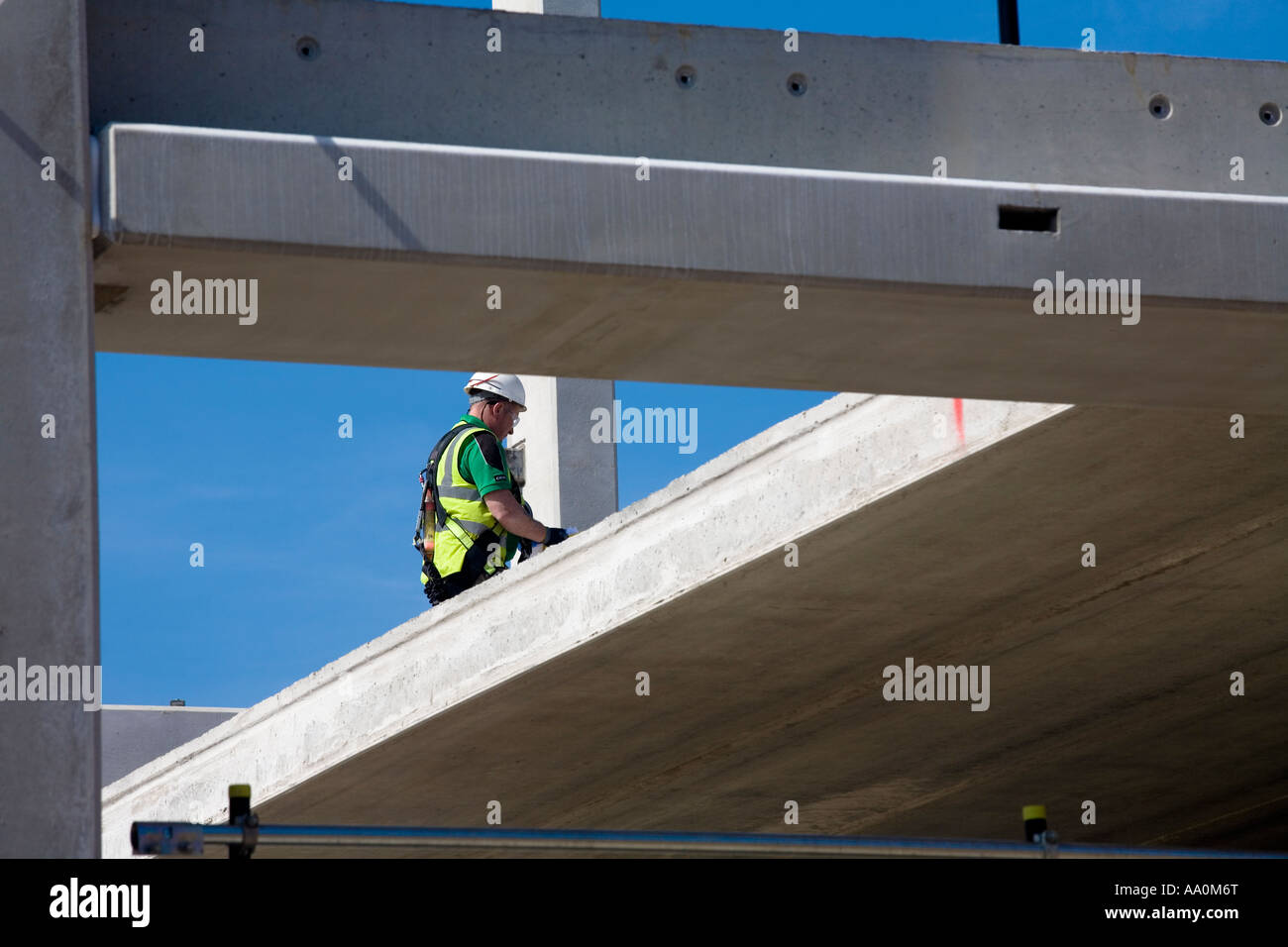 Construction worker working at height with no edge protection wearing hard hat safety harness and hi vis Stock Photo