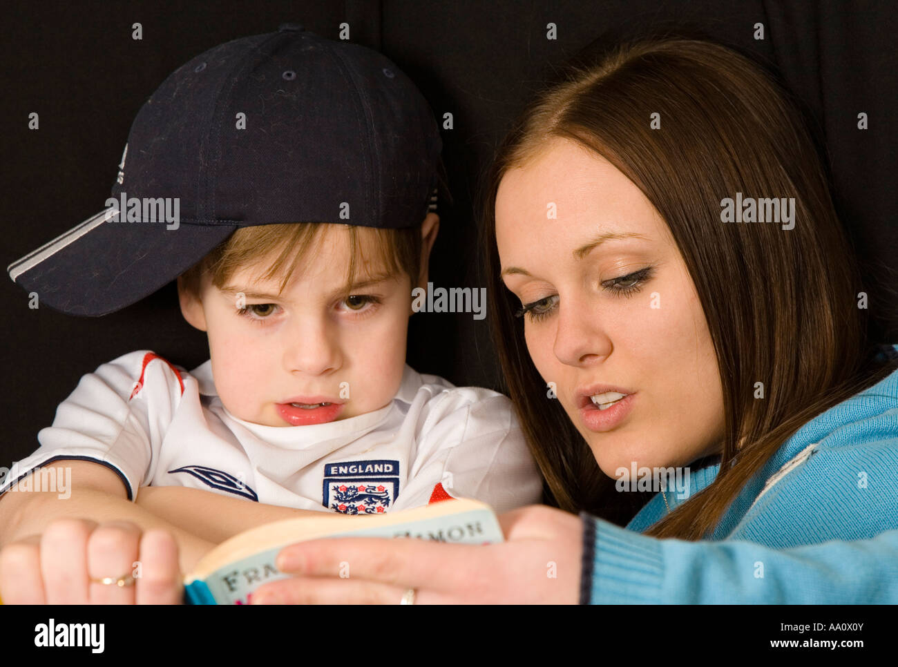 Sister reading a book to younger brother - Stock Image