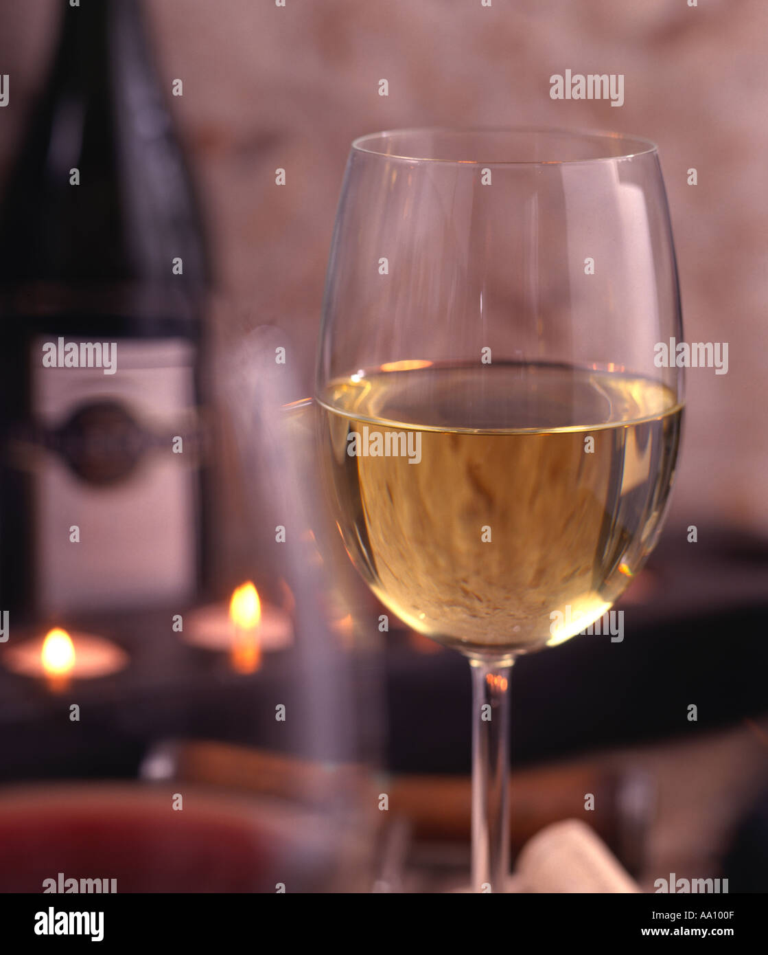 3109148288ff large glass of white wine with candles and bottle in the background ...
