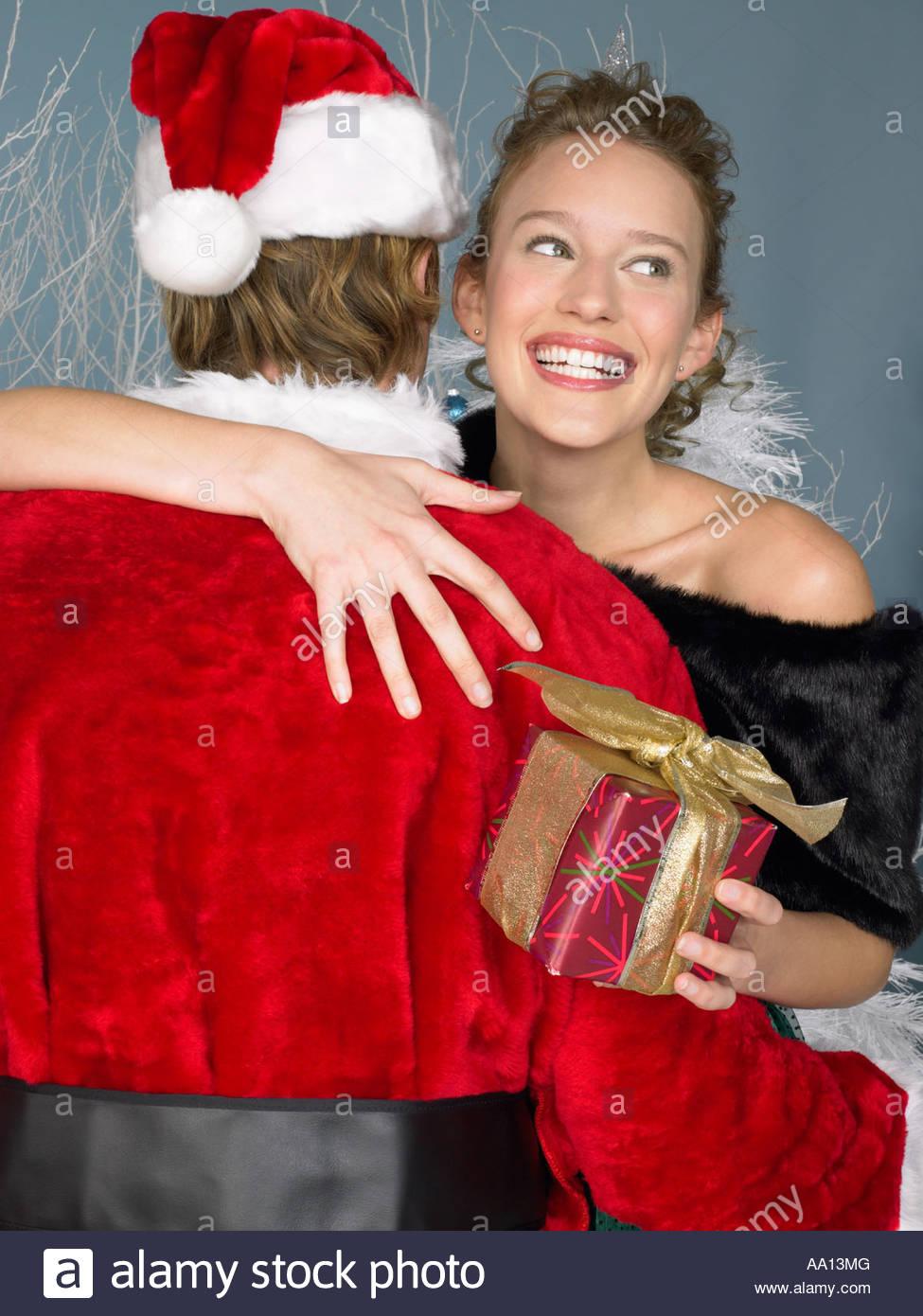 0f4ac368230 Woman hugging santa - Stock Image Woman hugging santa. AA13MG (RF). Rear  view of a young woman wearing a Santa hat ...