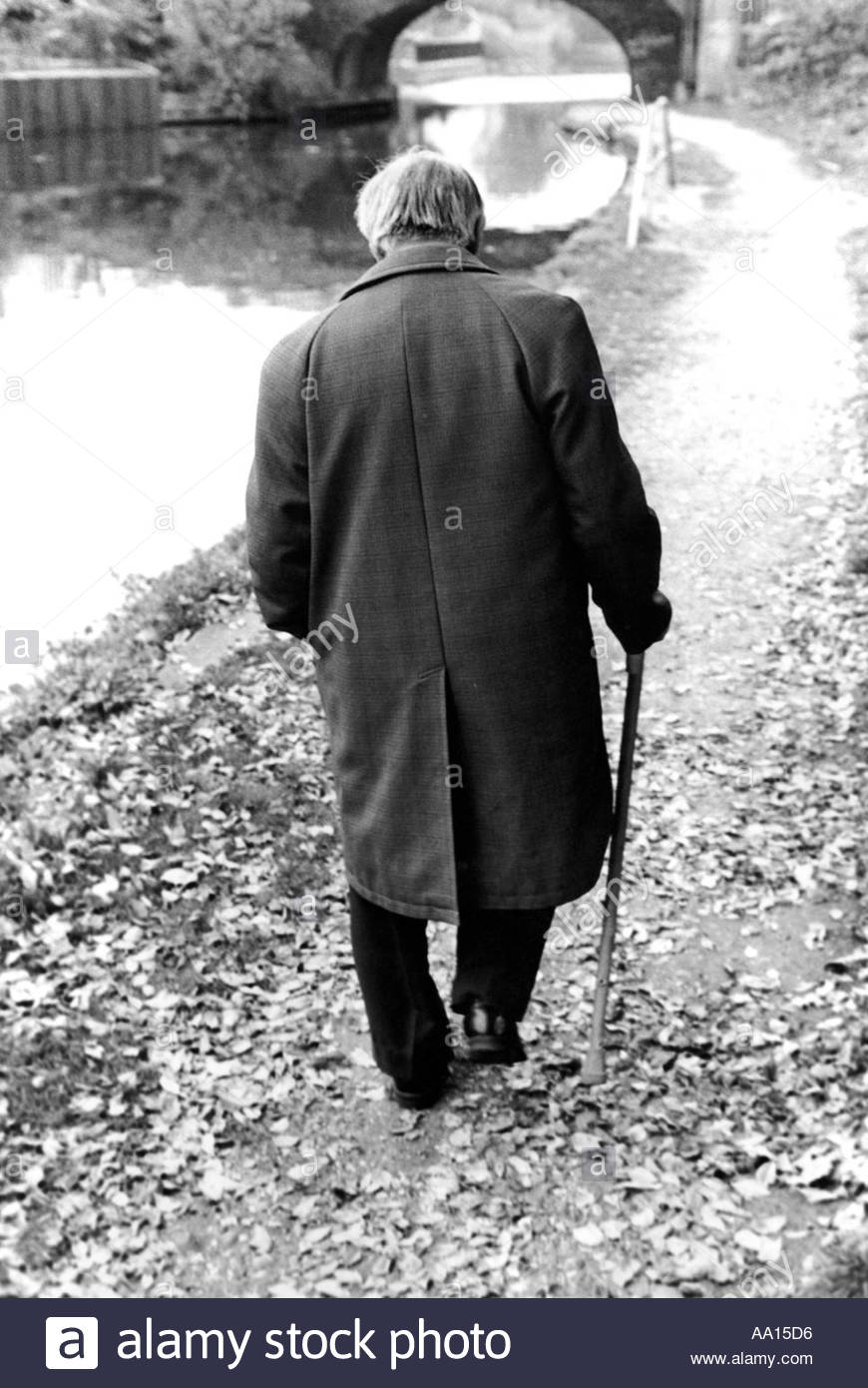 Elderly man walking along canal towpath using a stick East London UK - Stock Image