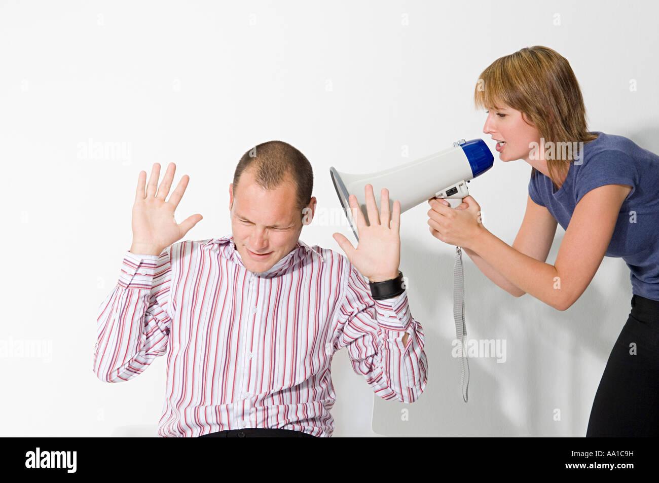 Man shouting at man through loudspeaker - Stock Image