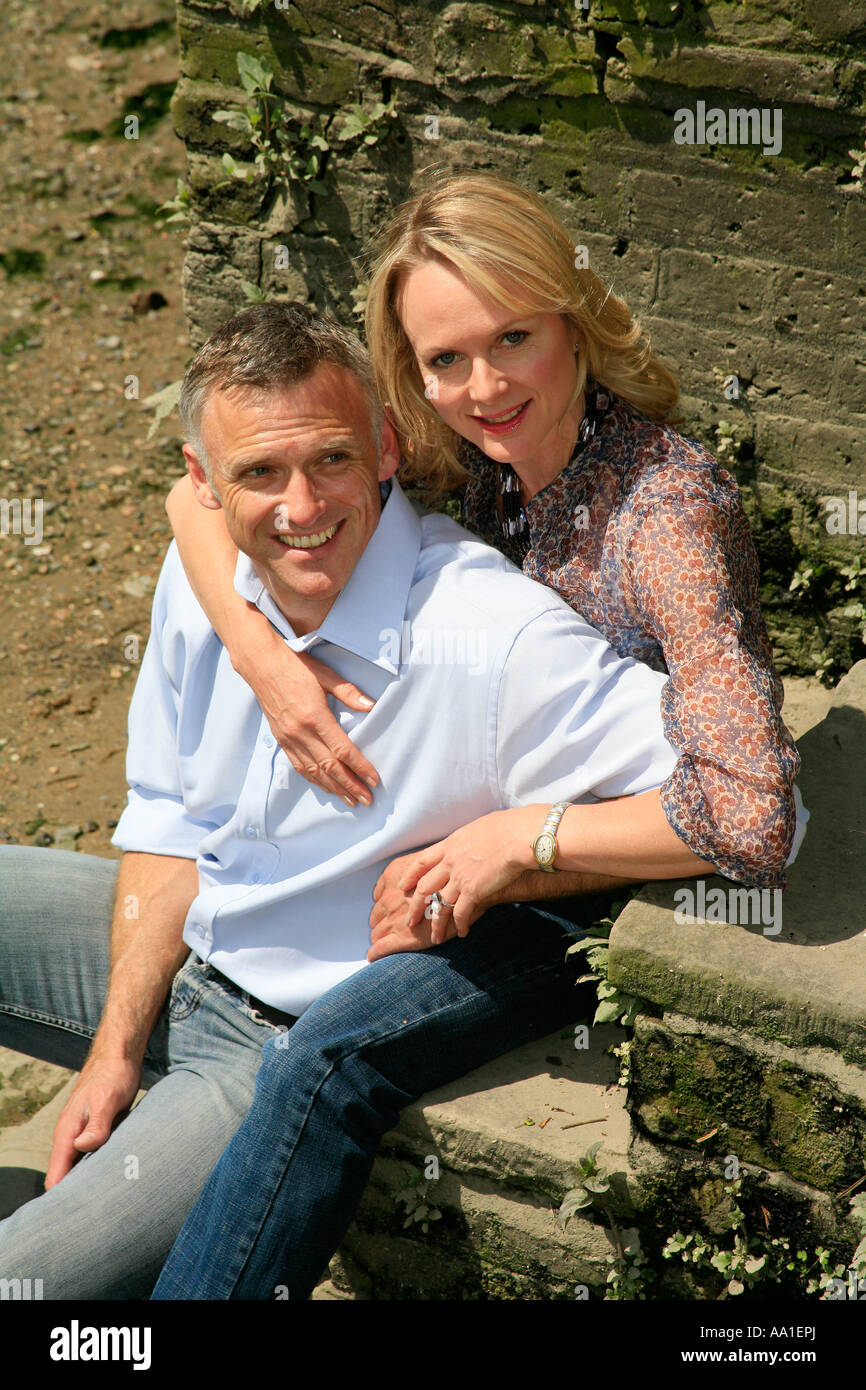 Happy middle aged couple sitting on steps - Stock Image