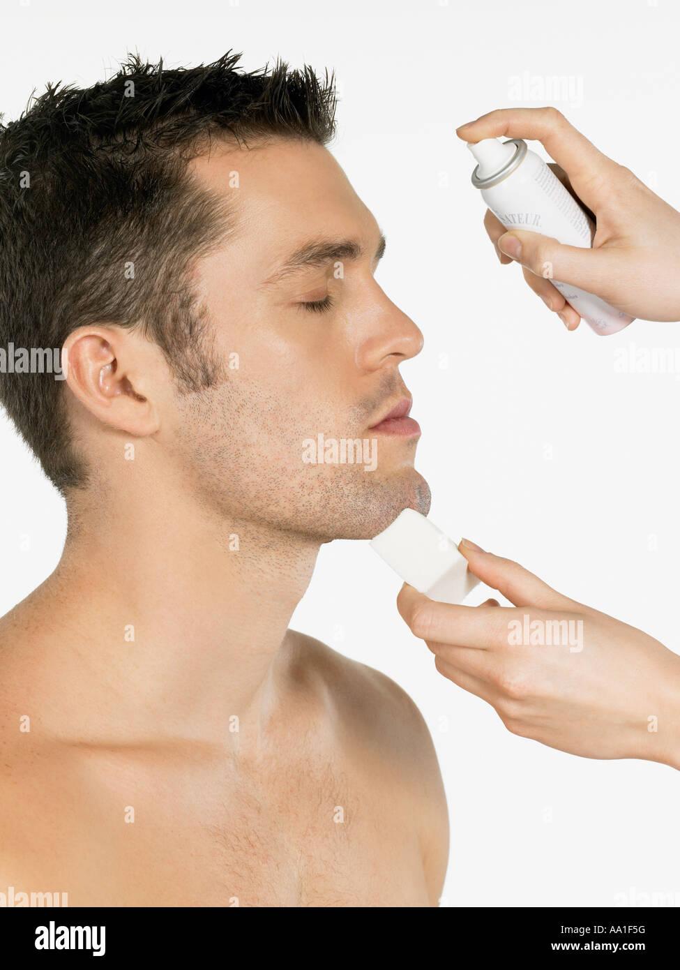 Man having water sprayed on his face Stock Photo