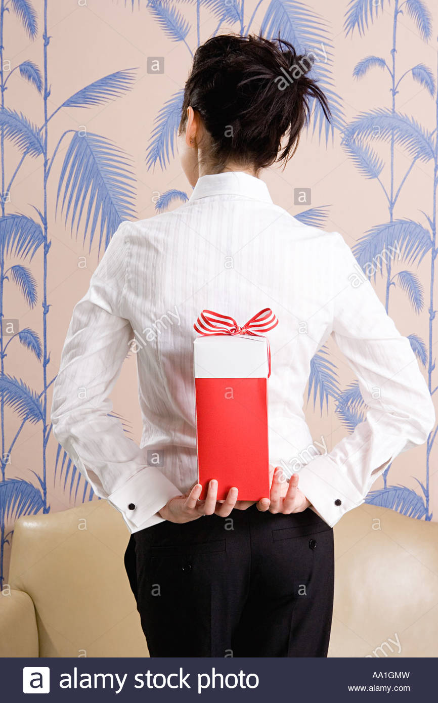 Young woman with a gift behind her back - Stock Image