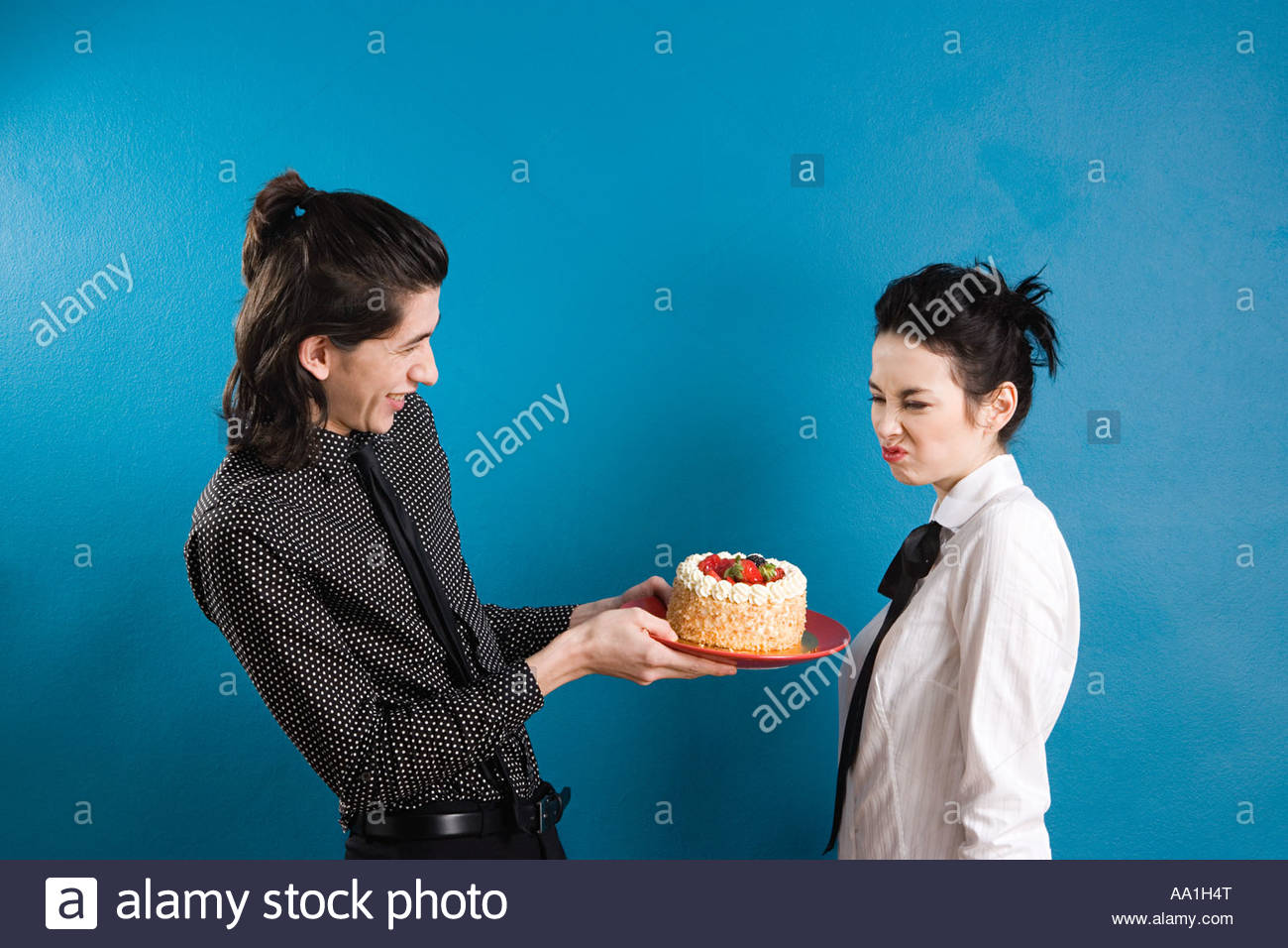 Man offering cake to grimacing woman - Stock Image