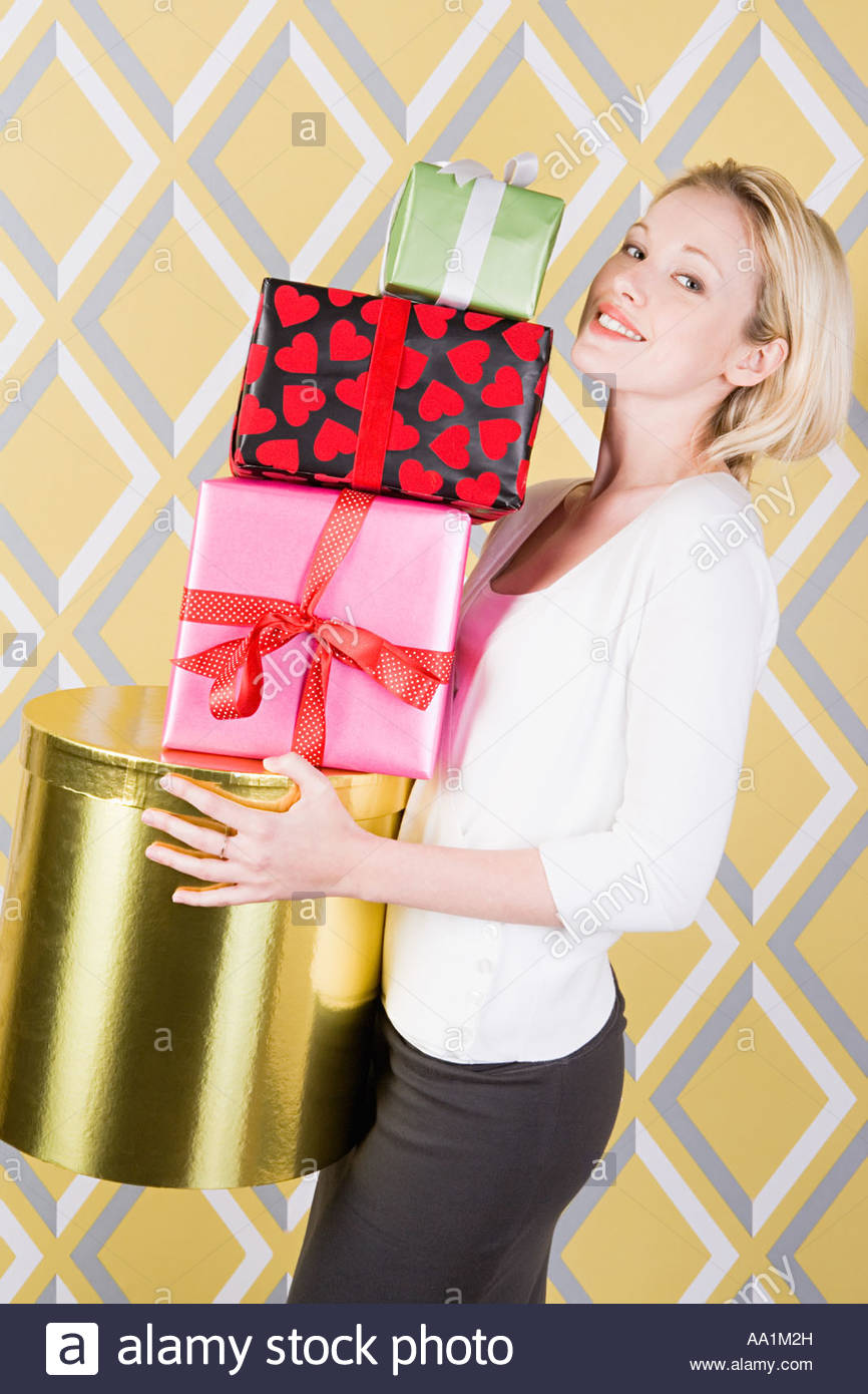 Woman with stack of presents - Stock Image