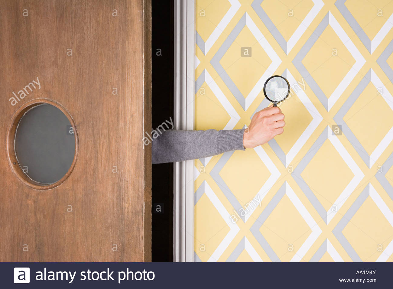 Person holding magnifying glass - Stock Image