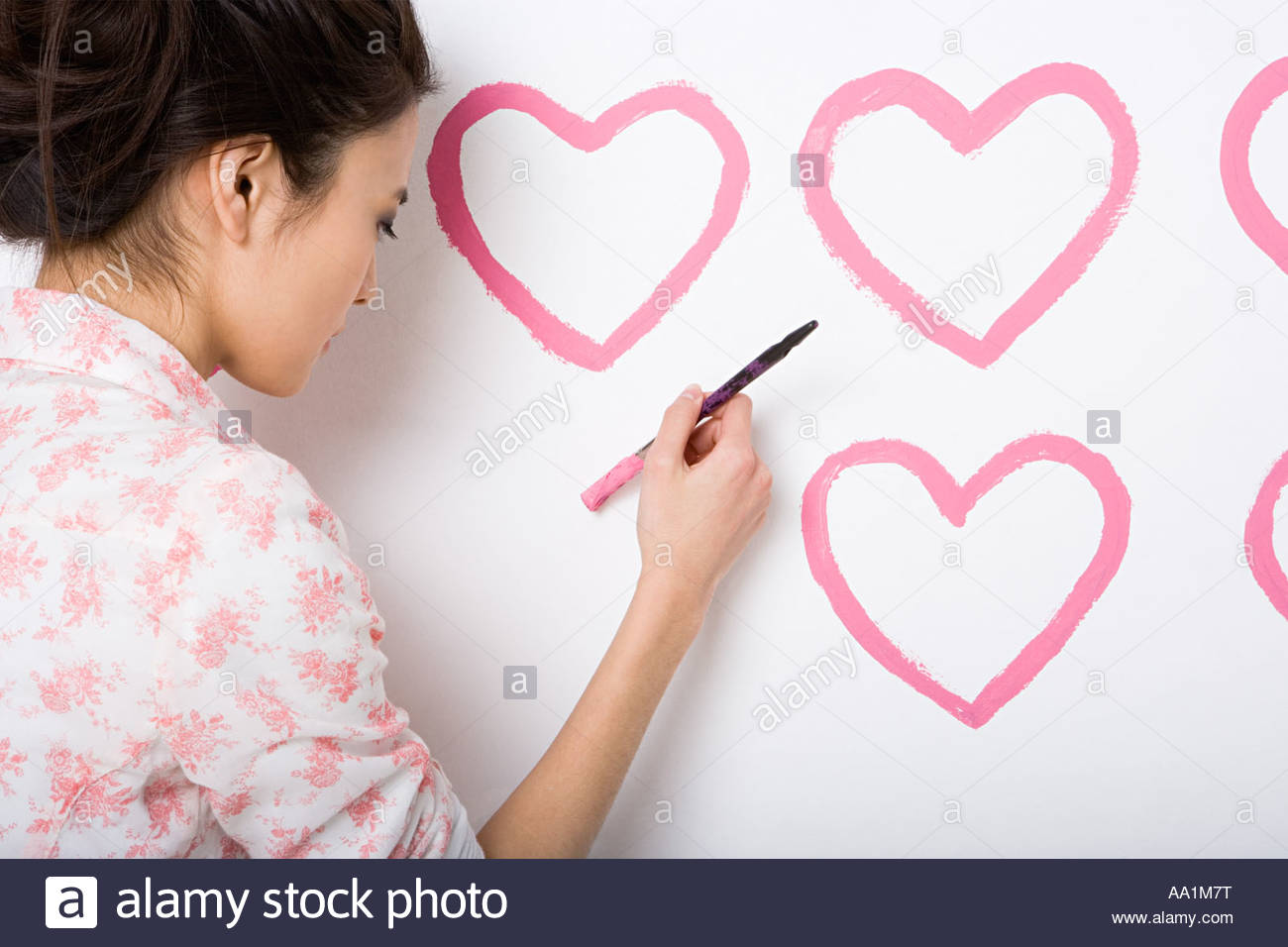 Young woman painting hearts on wall - Stock Image
