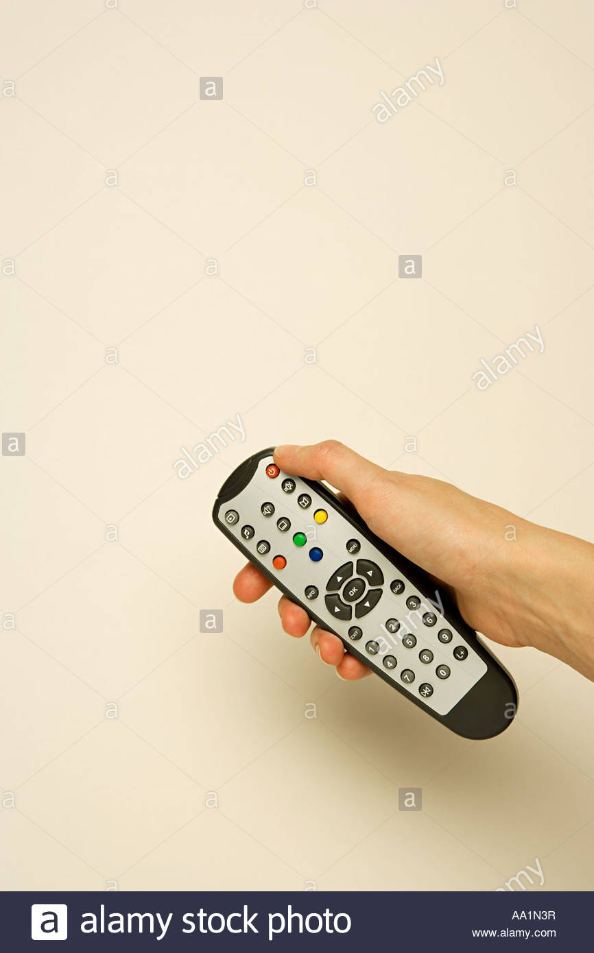 Person holding remote control - Stock Image
