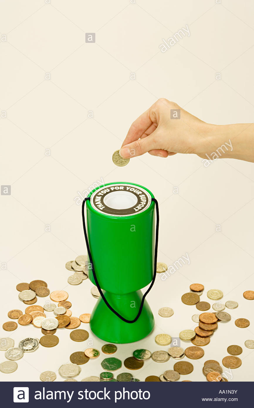 Person putting coin into donation box Stock Photo