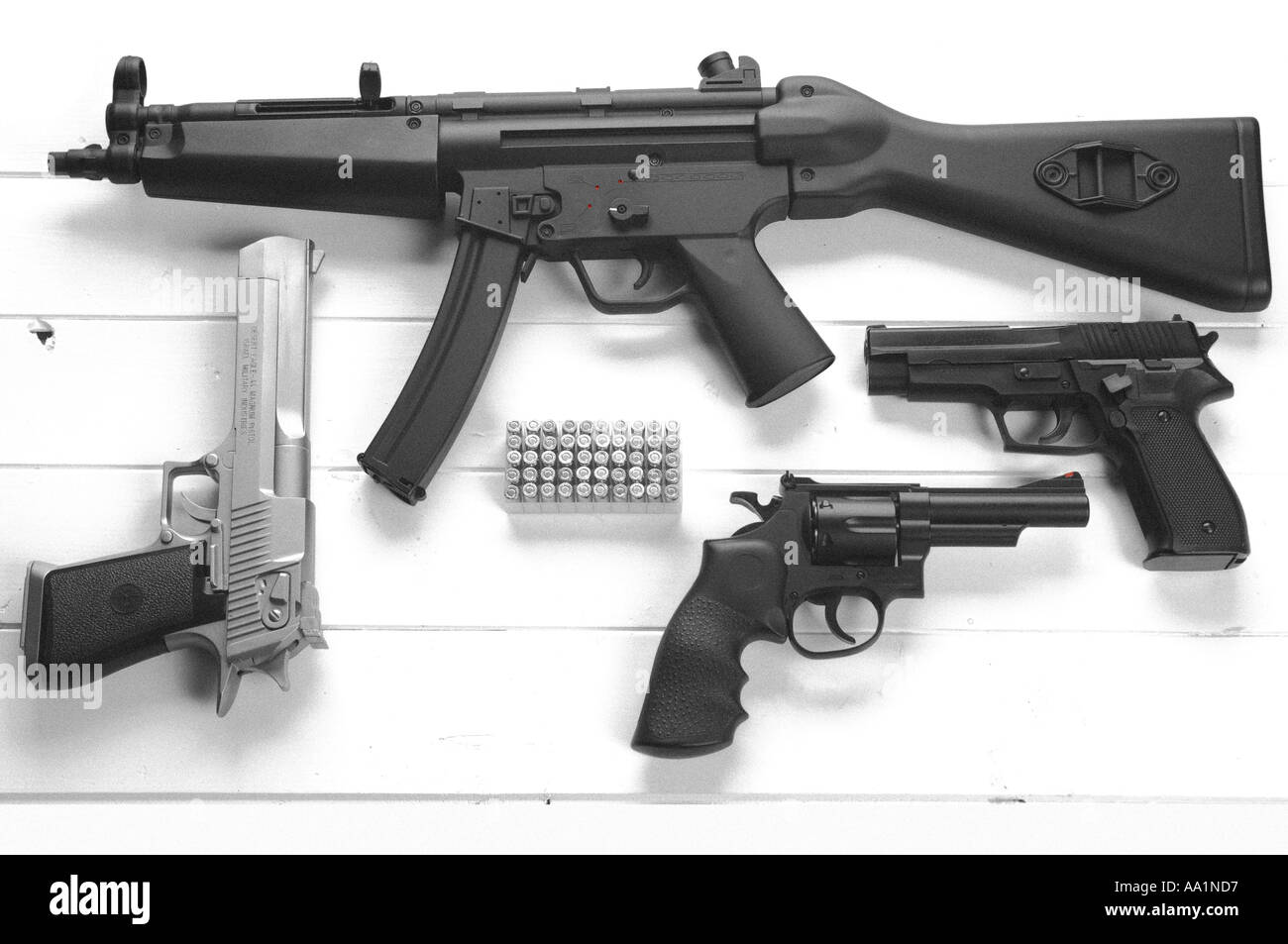 a collection of guns and ammunition including a heckler and koch MP5 desert eagle glock and 357 magnum pistols - Stock Image