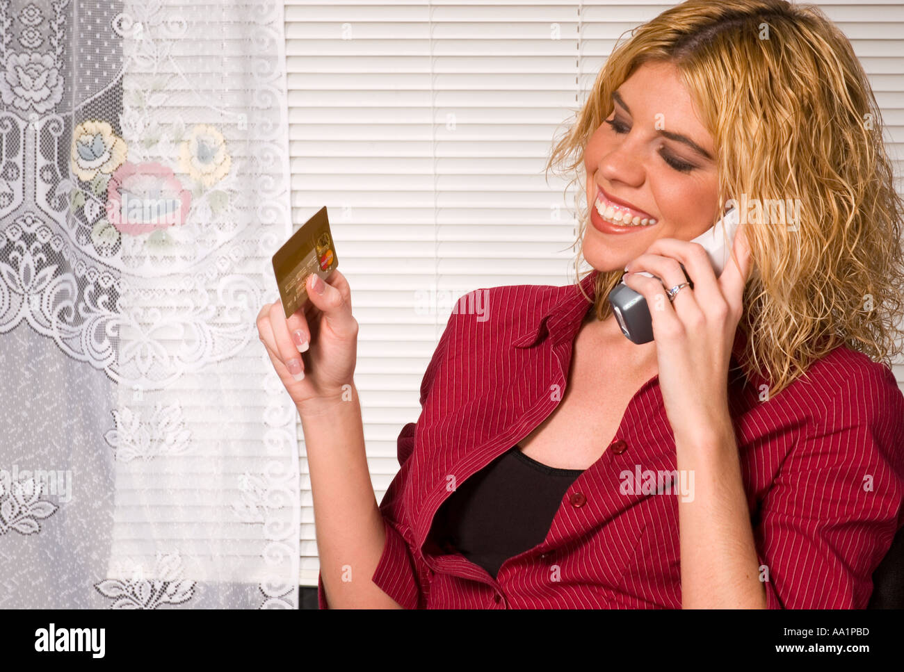 Young woman smiles and gives credit card number over phone USA Stock Photo