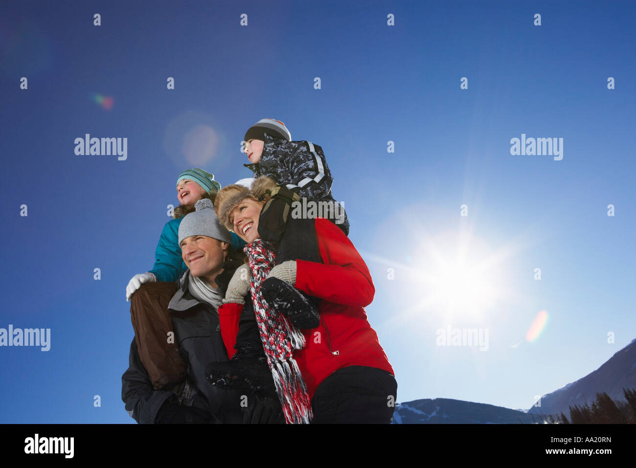 Parents Giving Children Piggyback Rides Stock Photo