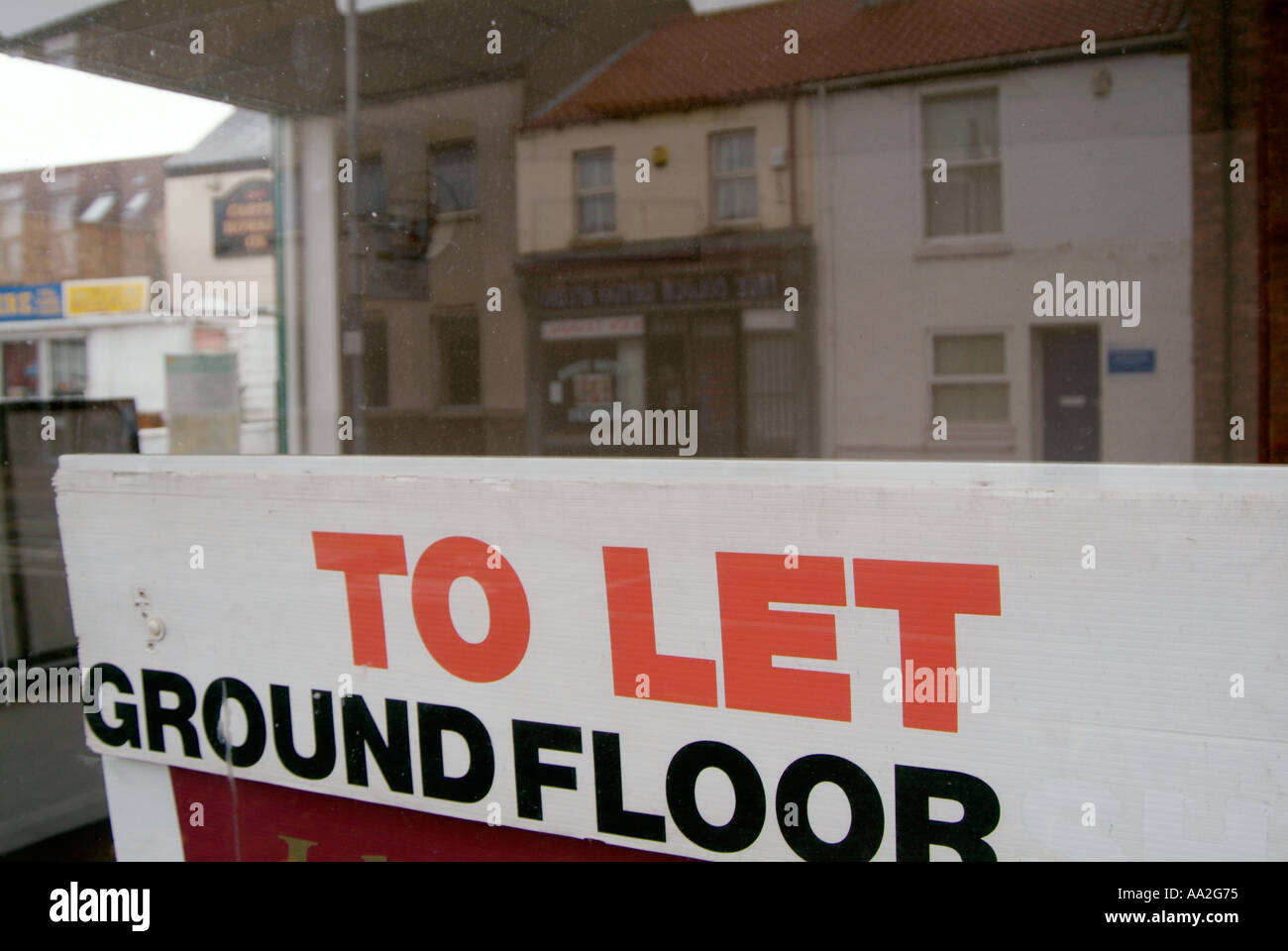 to let sign in shop window estate agent real property rent borrow high st street decline vacant empty - Stock Image