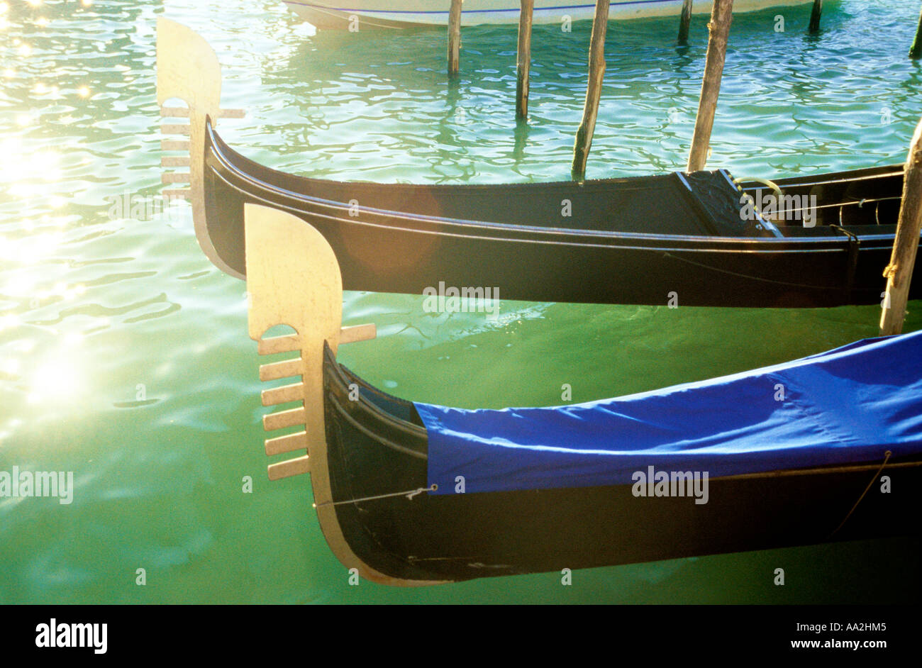Italy, Venice, gondolas in sun on water surface Canale Grande Grand Canal, carved prows of gondolas moored by canal Stock Photo