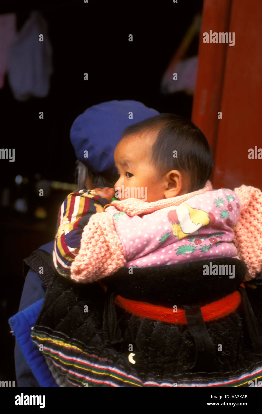 Chinese woman, Naxi woman, grandmother, carrying baby on back, grandchild, ethnic minority, Old Town, Lijiang, Yunnan Stock Photo