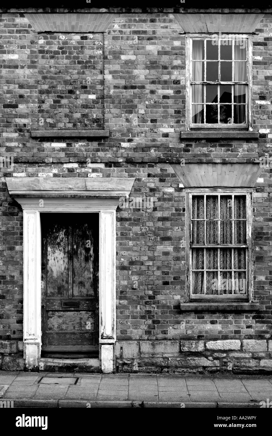 A run down Georgian terraced house desperately in need of some tender loving care. Black and White version (Portrait - Stock Image
