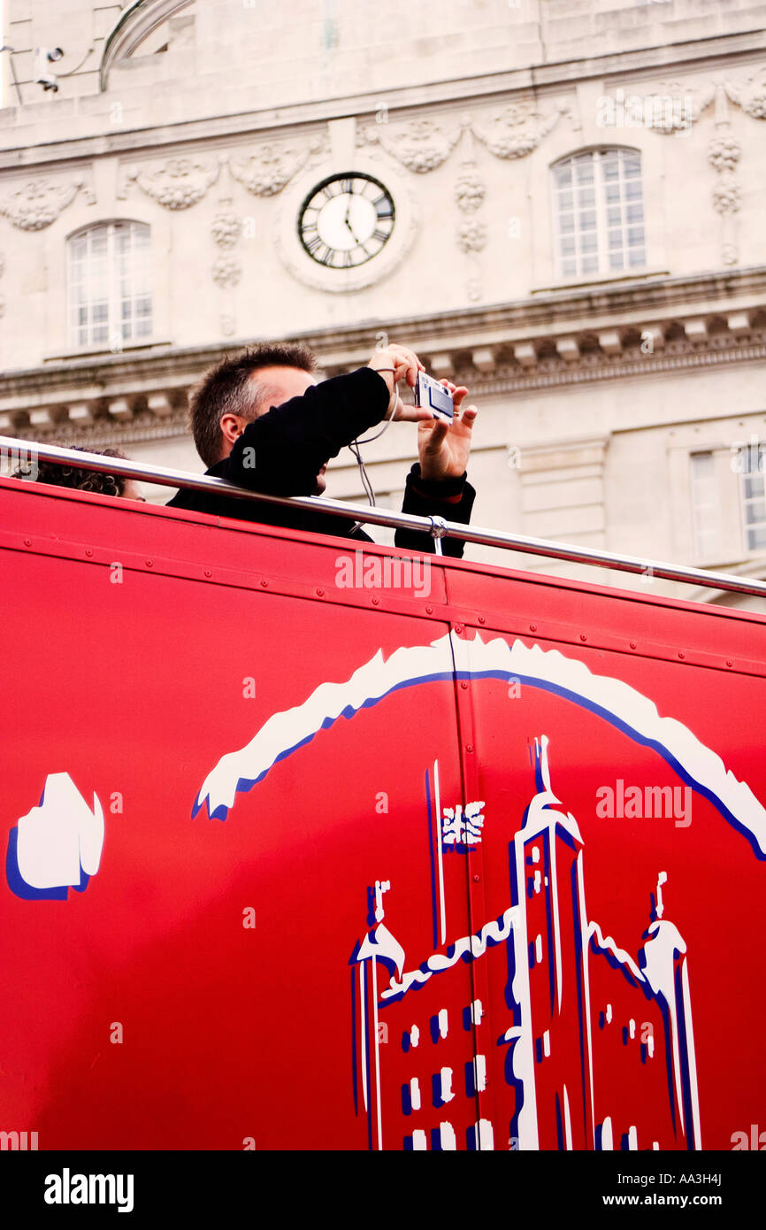 a tourist on  open deck red london bus taking picture - Stock Image