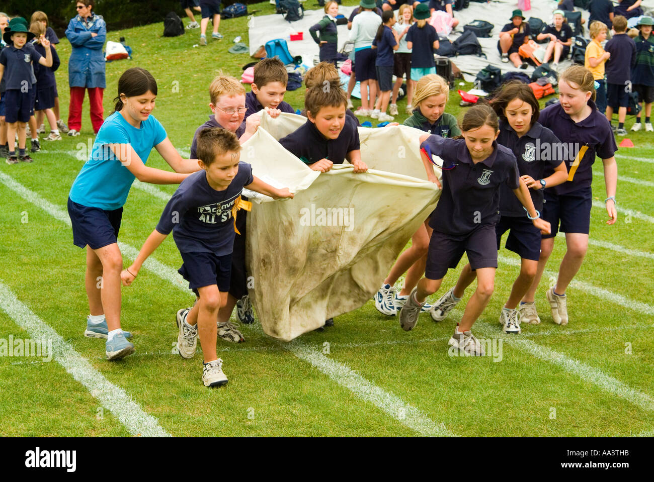 Children running in a sack relay race at primary school sports day in Hobart Tasmania Australia - Stock Image