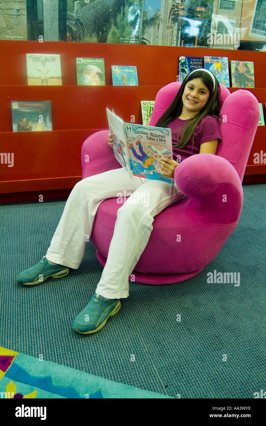 A Young Girl In A Library Sitting In A Fun Chair Shaped Like A Hand
