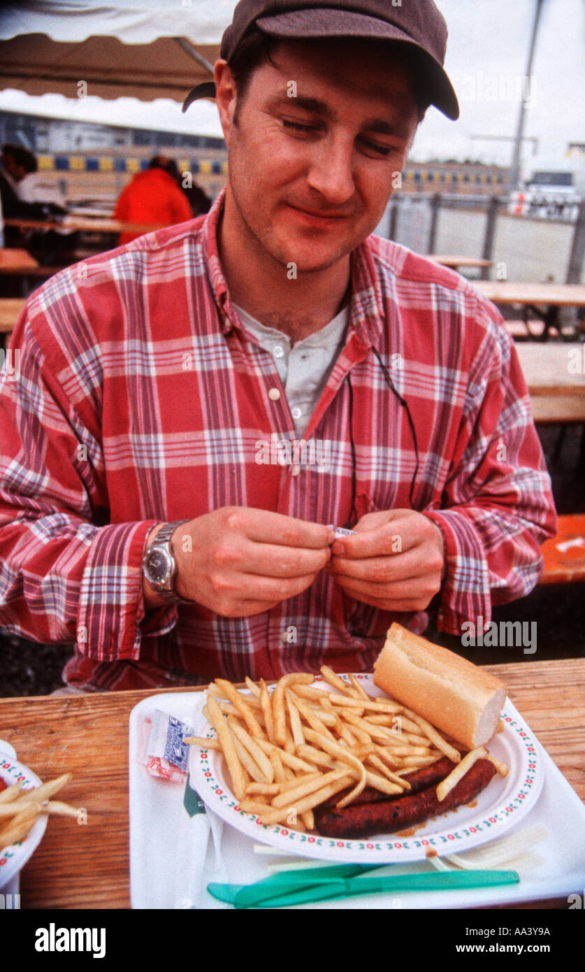 Man wearing a baseball cap and striped shirt with a plate of steak and chips in front of him - Stock Image