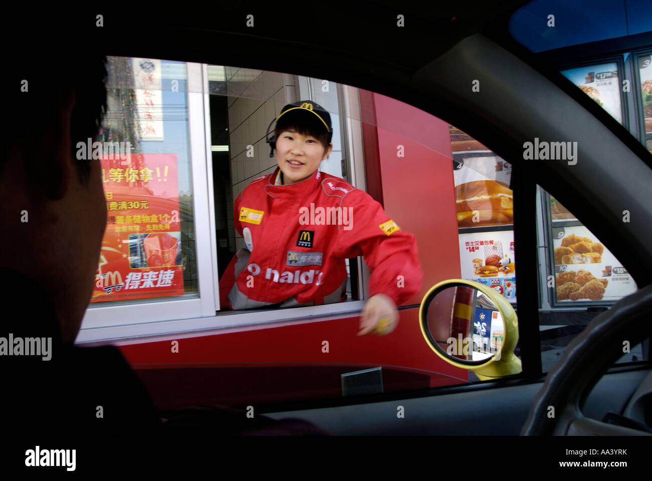 A chinese employee serves a driver in the first Sinopec McDonald's Drive Thru in Beijing China 12 APR 2007 - Stock Image