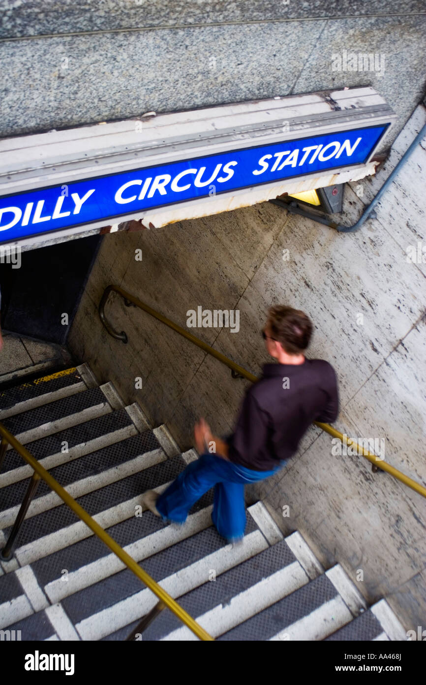 a man rushing down the stairs to london's undergroung picadilly circus - Stock Image