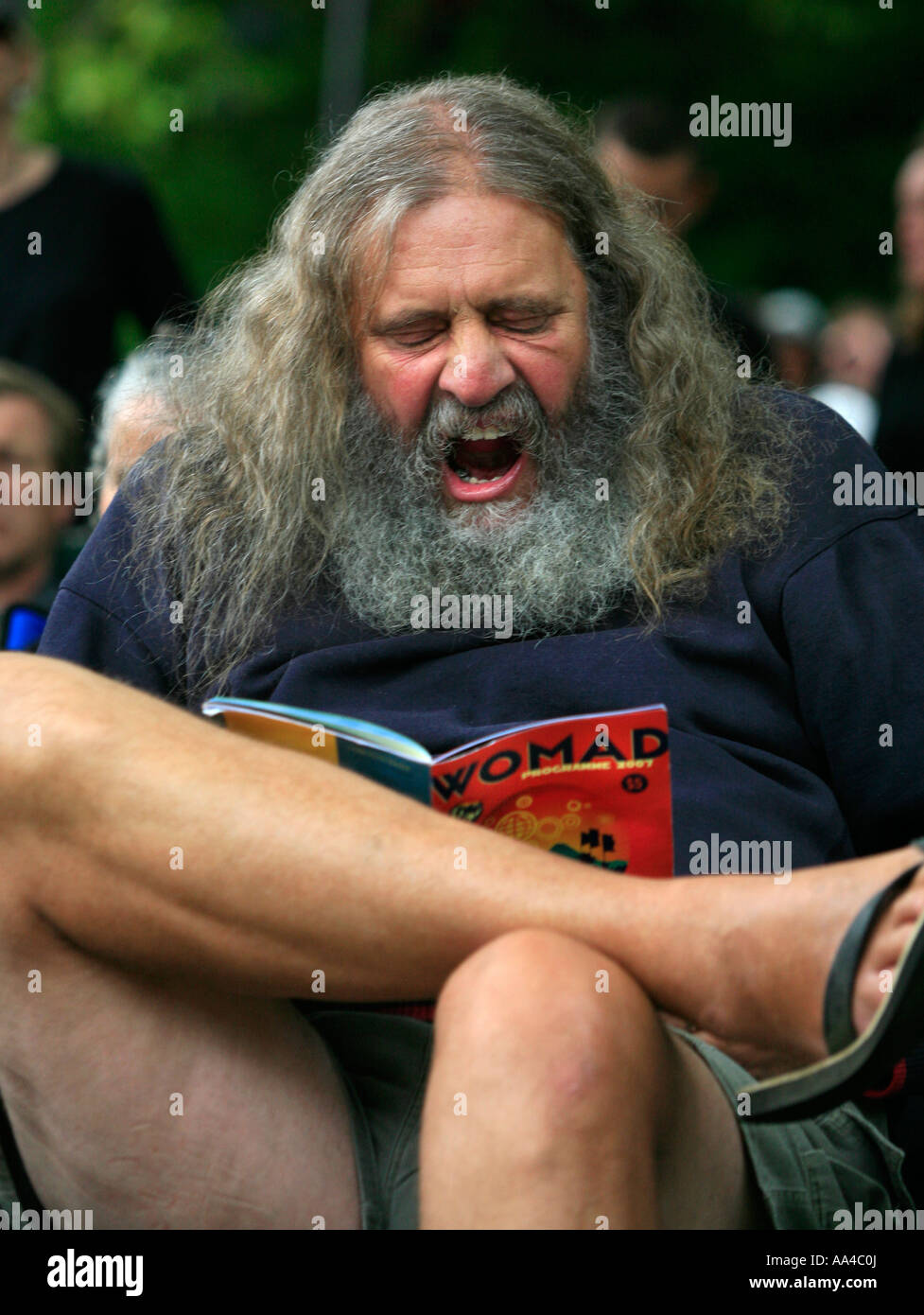 A big hairy bearded man yawning as though bored at a music concert in New  Zealand