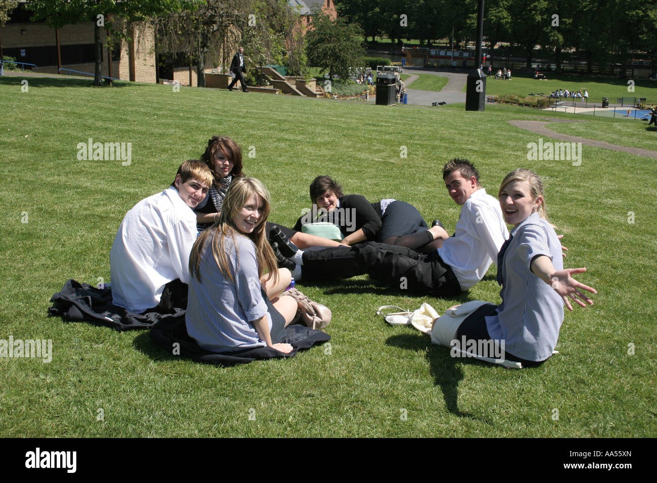 Secondary school children lazing in the sun in Abbey Park in Evesham. - Stock Image