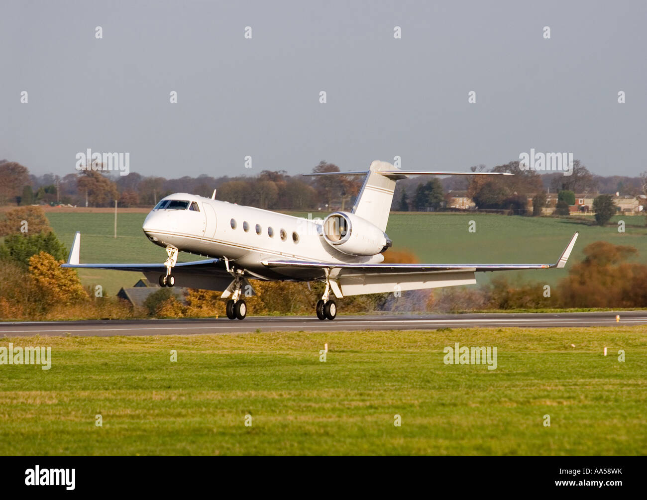 Gulfstream Aerospace G IV executive jet touching down on an airport runway - Stock Image