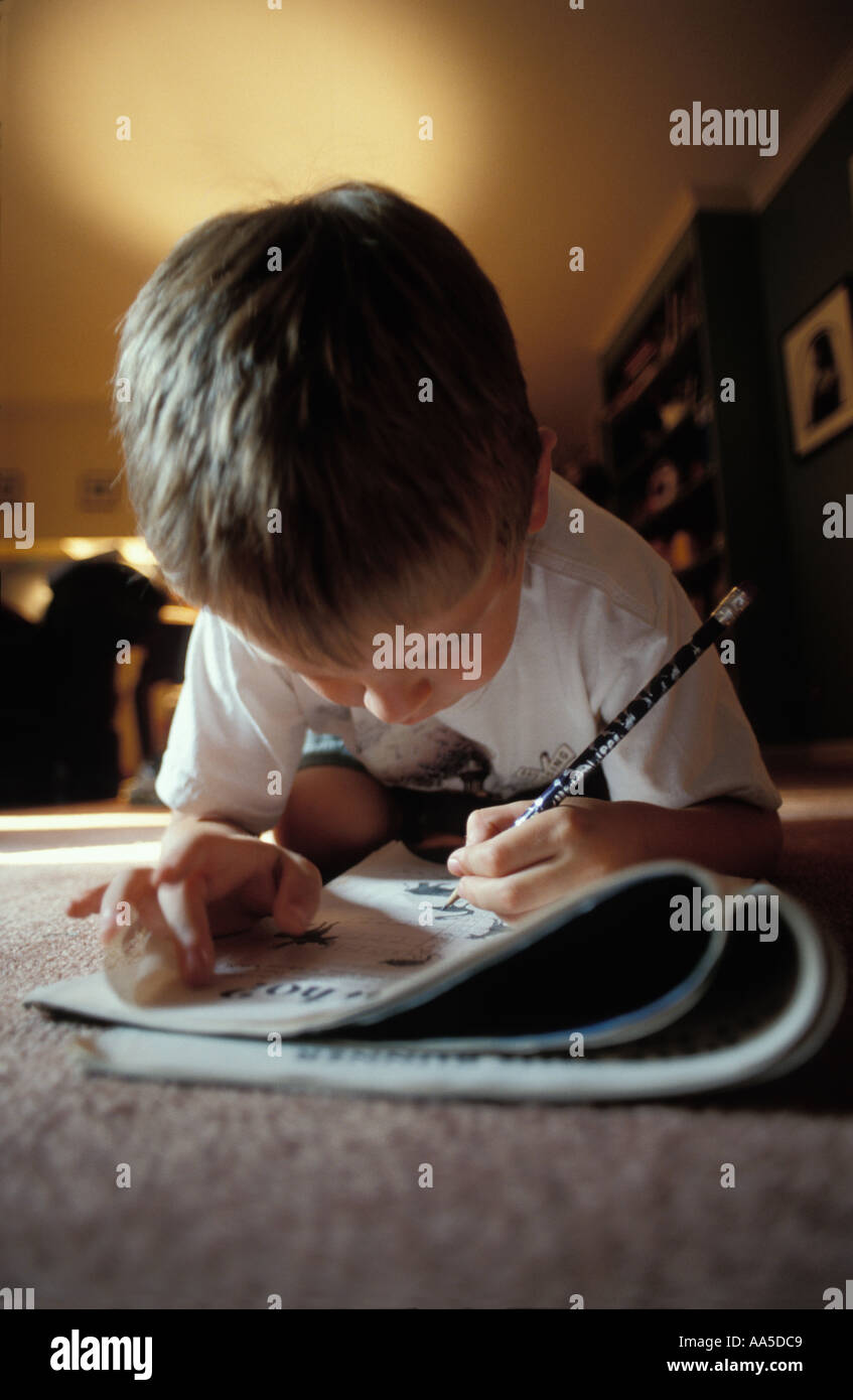 Young boy age 5 working on a word puzzle while laying on the floor - Stock Image
