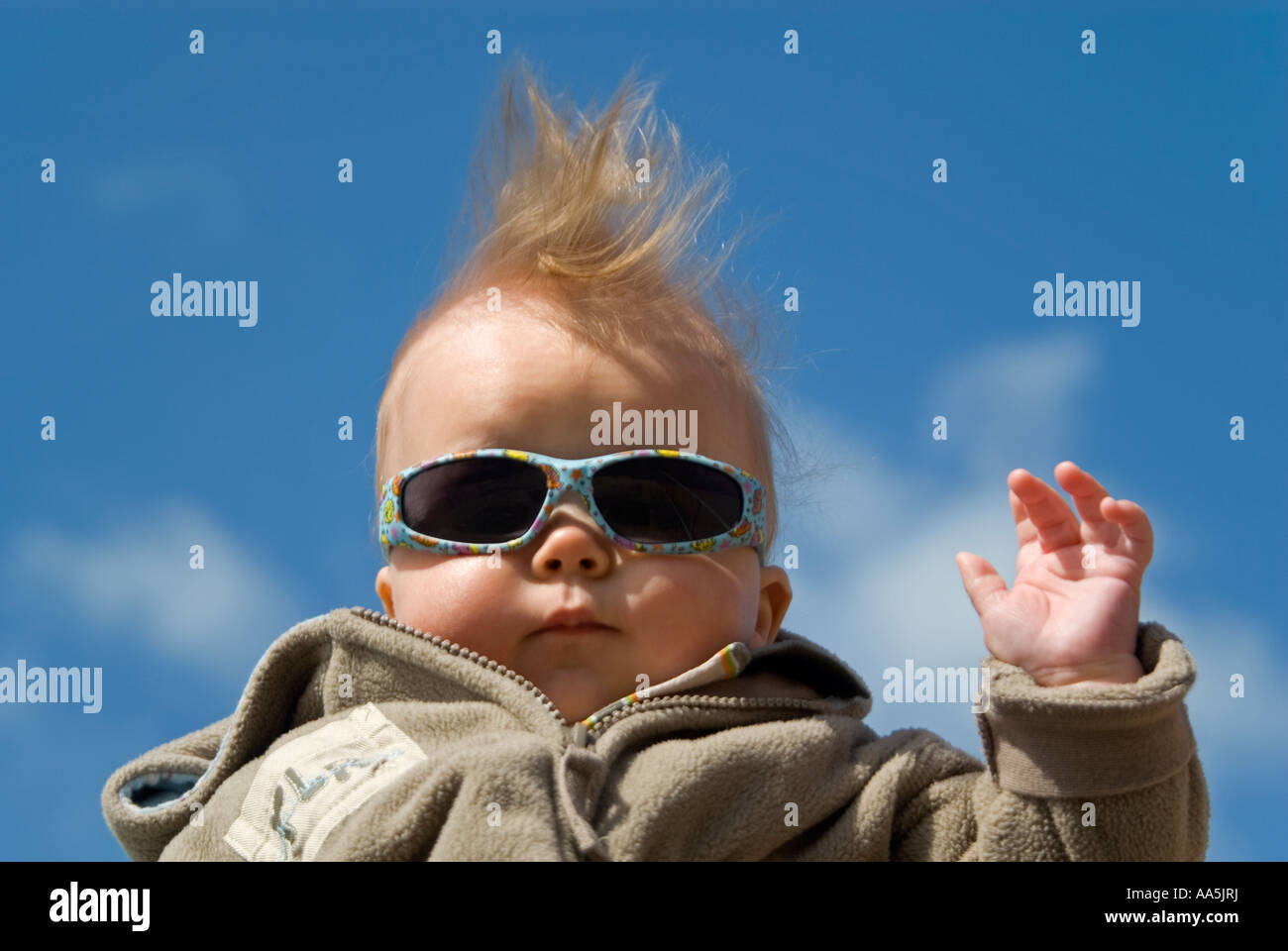 Humorous horizontal close up of a 6-month old baby boy posing for photographs. - Stock Image