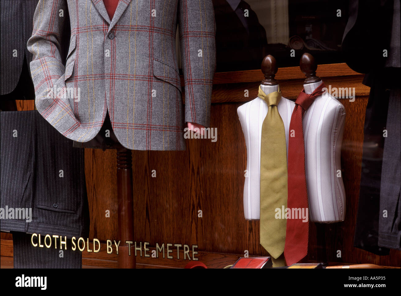 Savile Row tailor shop window with miniature judies and ties, wool jacket, pin striped trousers & sign: Cloth Sold By The Metre - Stock Image