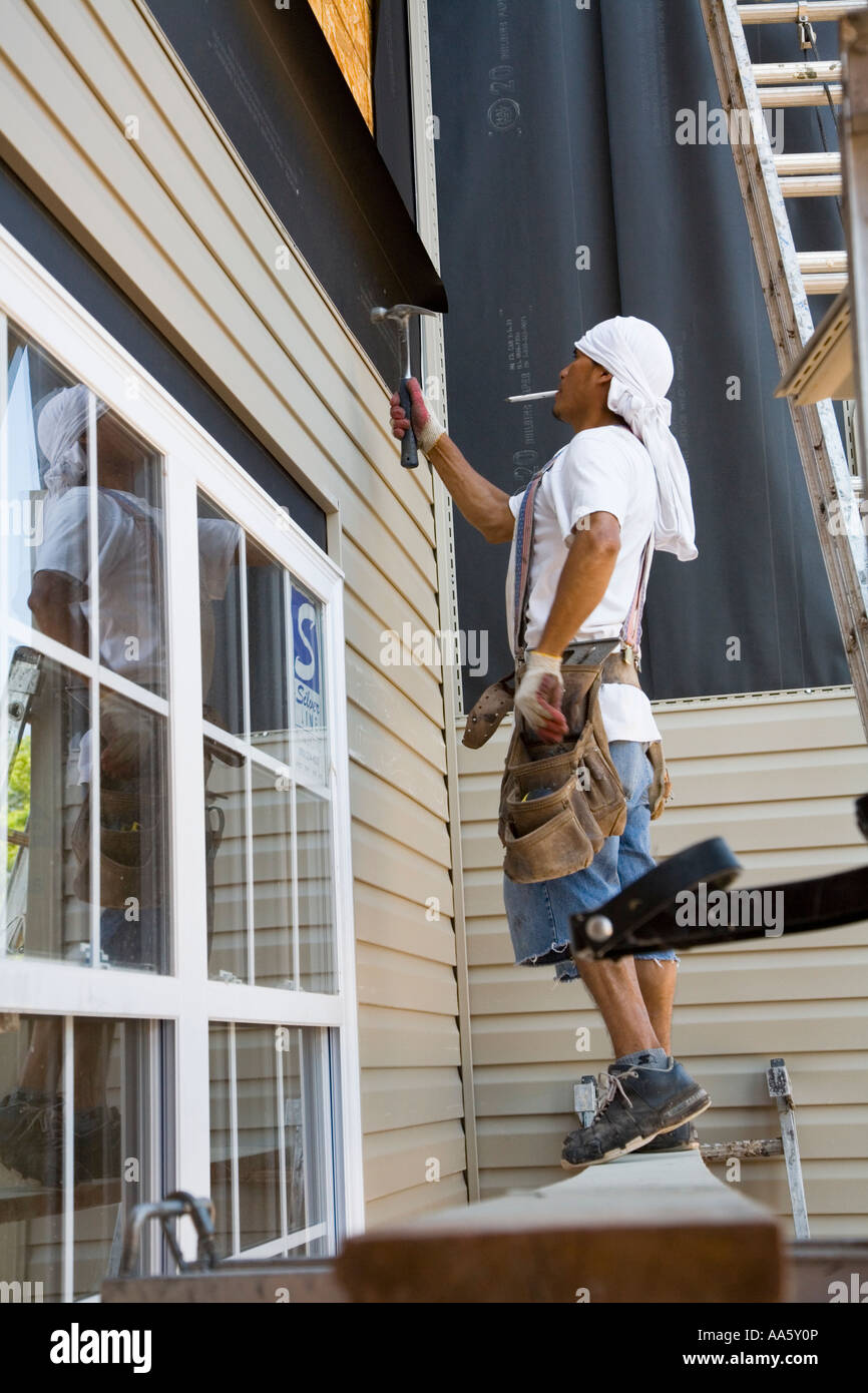 Immigrant Workers Installing Vinyl Siding Stock Photo