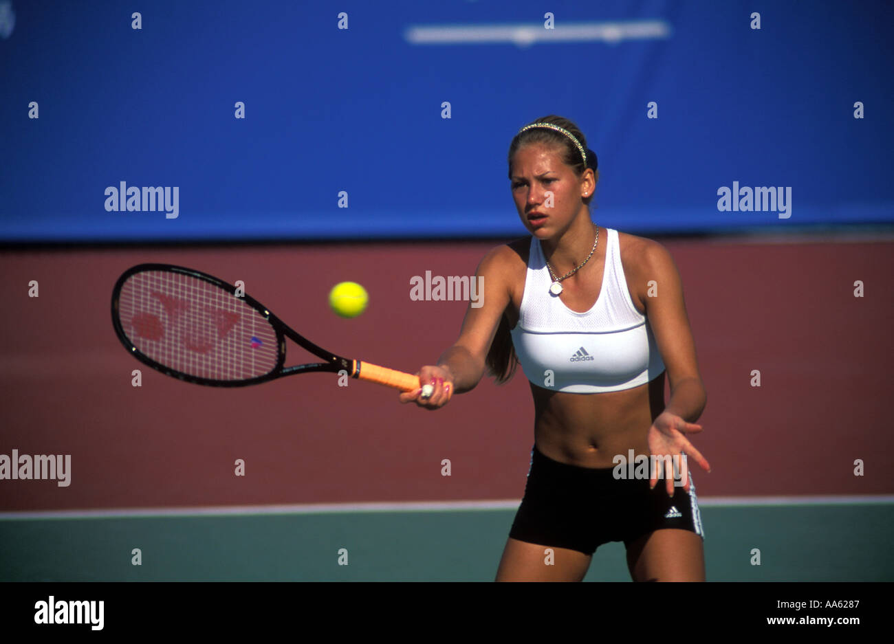 309be7554fa3 Anna Kournikova in a white crop top volleys at the net during a practise  session in Hong Kong