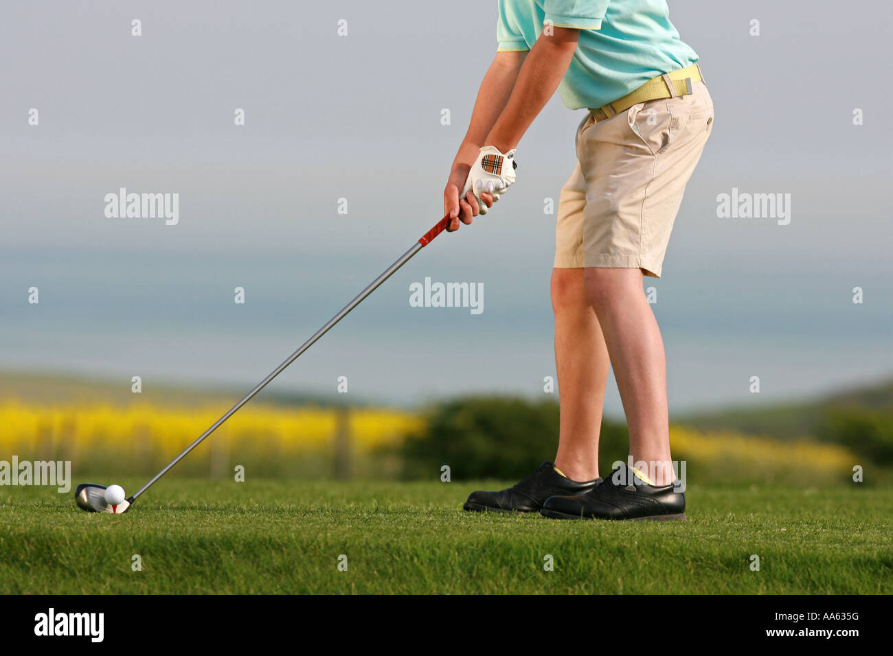 A young golfer prepares to tee off. - Stock Image