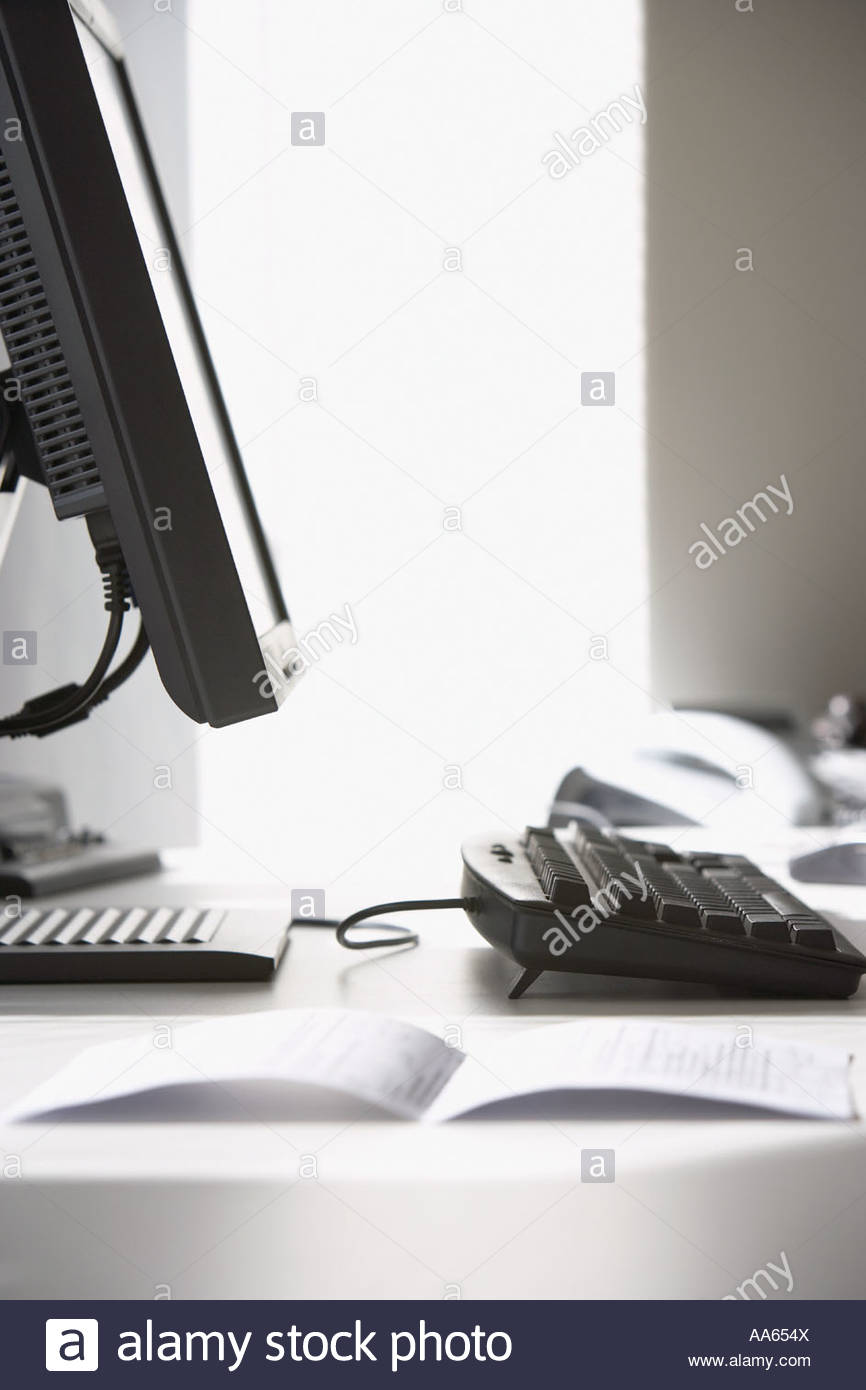 Detailed view of document on desk with computer - Stock Image