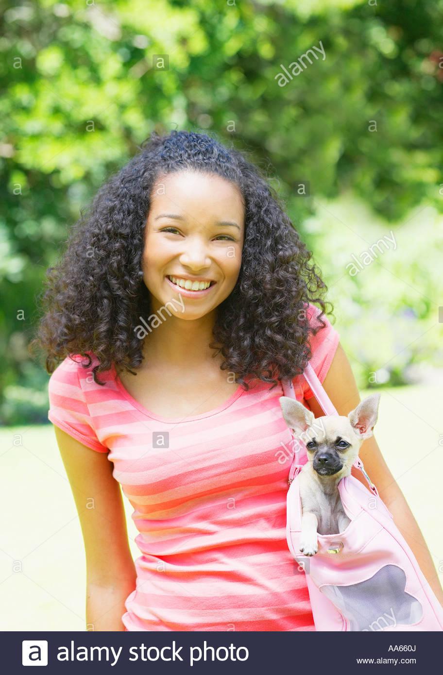 Teenage girl with puppy dog in handbag - Stock Image