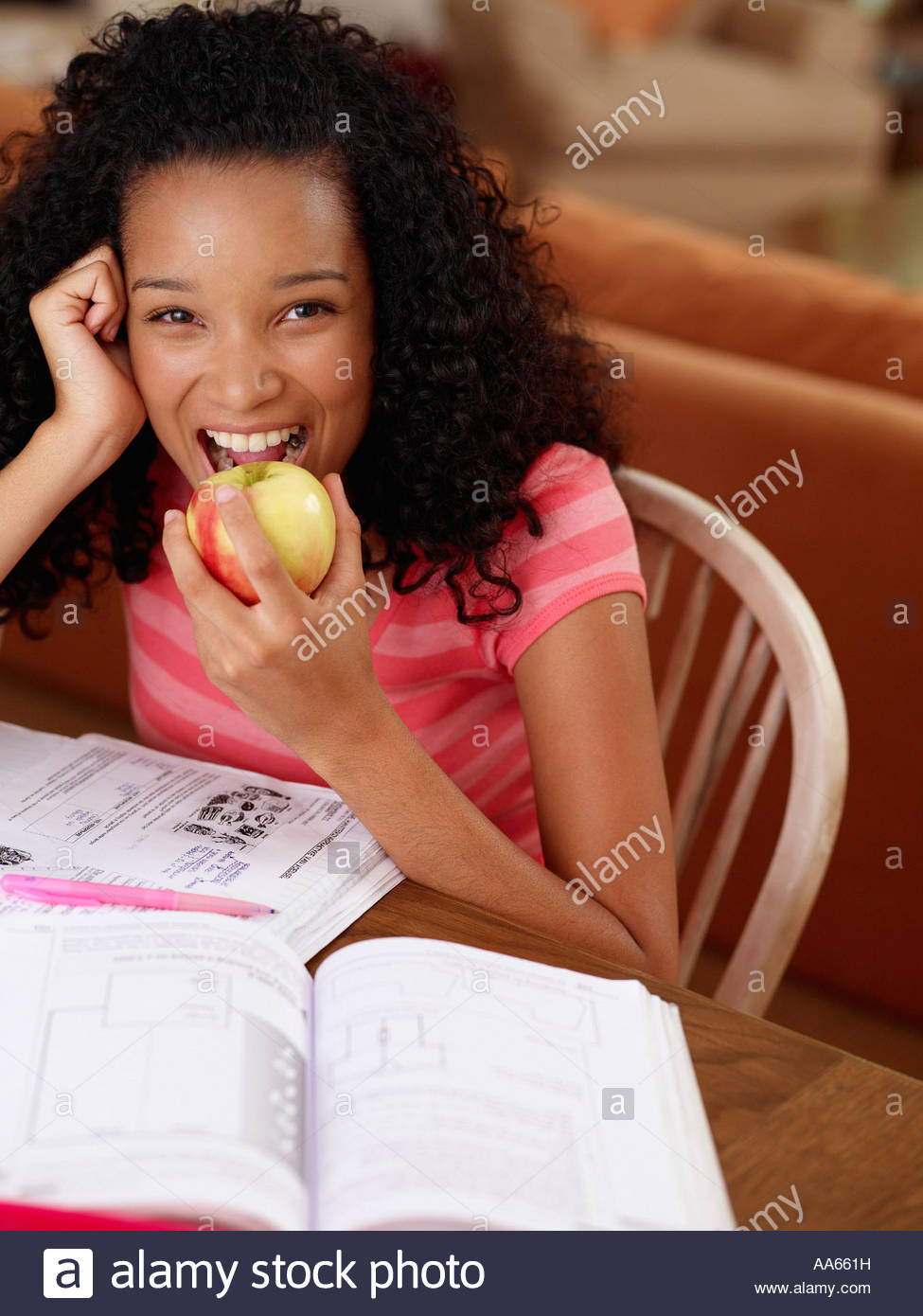 Teenage girl sitting at table with homework eating an apple - Stock Image