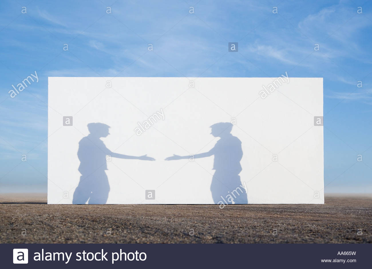 Man outdoors with hand extended in front of white wall - Stock Image